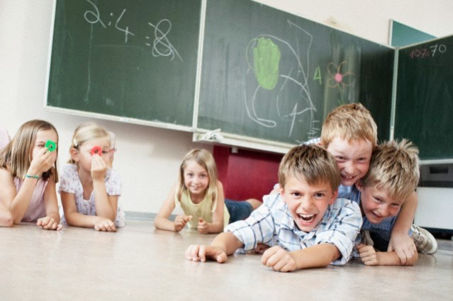 Children playing on floor in classroom --- Image by © Oliver Rossi/Corbis